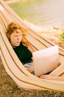 Mujer que trabaja en la computadora portátil en hamaca