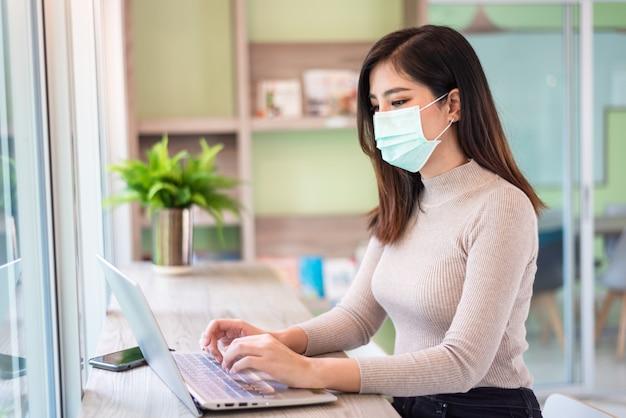 Mujer que trabaja en la computadora portátil con una máscara médica
