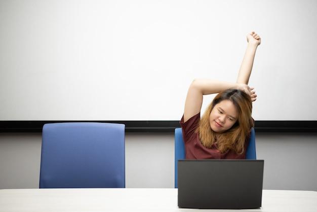 Mujer que trabaja por computadora portátil en la oficina con relax