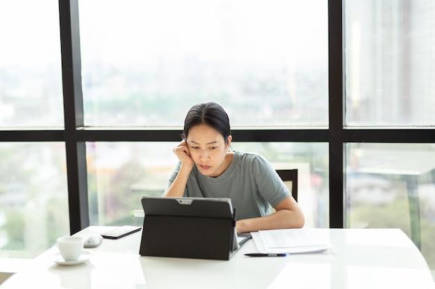Mujer que trabaja en la computadora portátil con el papeleo en la mesa durante la cuarentena