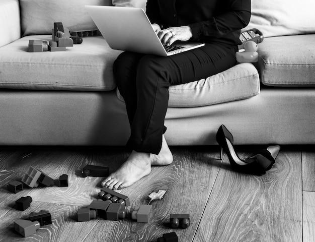 Mujer que trabaja en la computadora portátil en el sofá