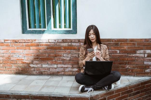 Mujer que trabaja con la computadora portátil y su teléfono móvil