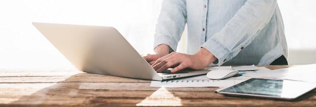Mujer que trabaja en una computadora portátil y tablet pc en interiores