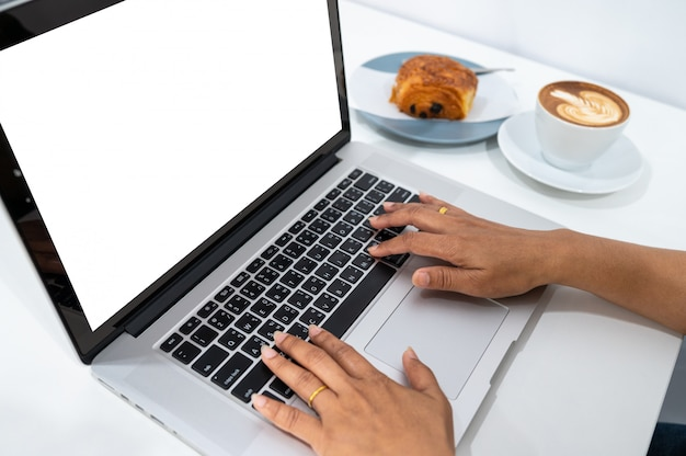 Mujer que trabaja en la computadora portátil con una taza de café en la mesa