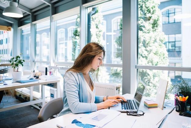 Mujer que trabaja con la computadora portátil
