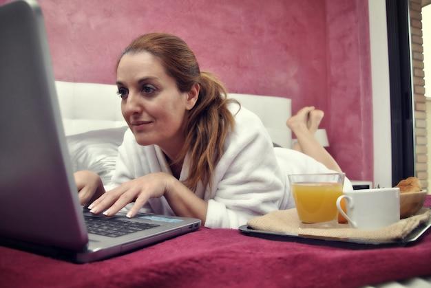 Mujer que trabaja con la computadora en su habitación en silencio