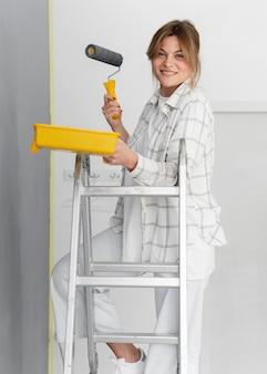 Mujer que trabaja con escalera