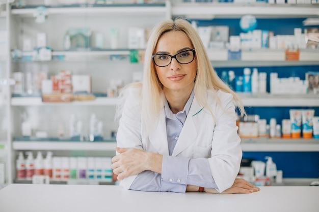 Mujer que trabaja en la farmacia y vistiendo abrigo