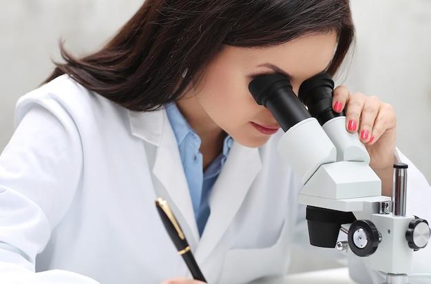 Mujer que trabaja en el laboratorio con un microscopio
