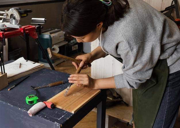 Mujer que trabaja con madera de tiro medio