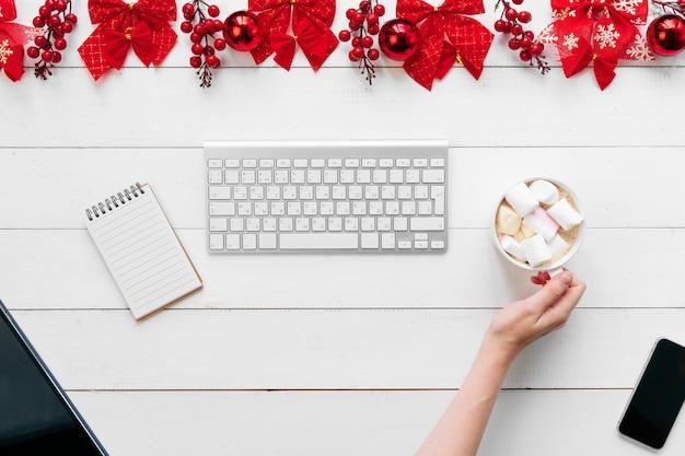 Mujer que trabaja en una mesa de oficina con decoraciones festivas de navidad