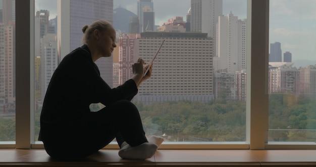 Mujer que trabaja en el negocio con la almohadilla sentada junto a la ventana