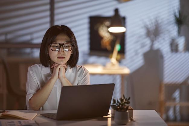 Mujer que trabaja en la oscura oficina