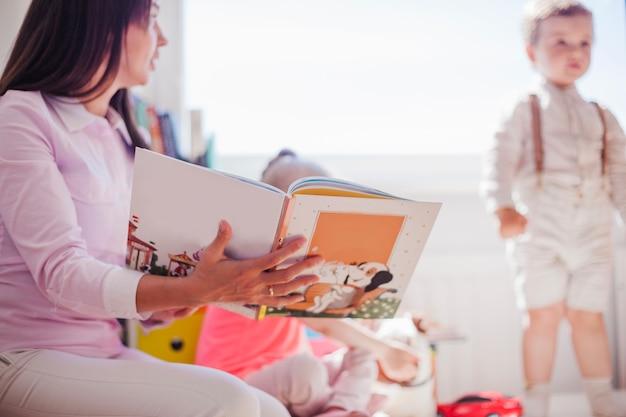 Mujer que trabaja en preescolar con los niños