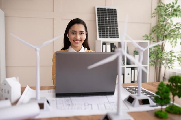 Mujer que trabaja en el proyecto de medio ambiente en la computadora portátil
