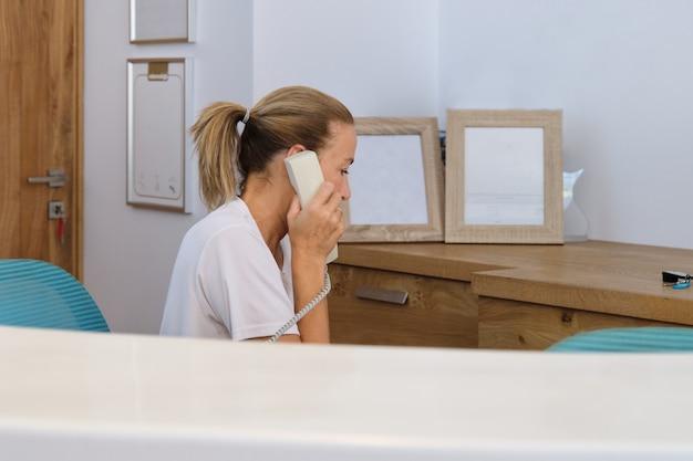 Mujer que trabaja en la recepción del hotel, hablando por teléfono comercial