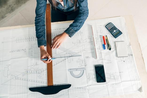 Mujer que trabaja con la regla y la pluma grandes en la tabla