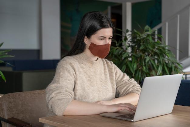 Mujer que trabaja sola mientras se aleja socialmente de otros compañeros de trabajo