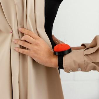 Mujer que trabaja en su taller de diseño de moda sola