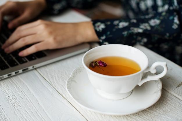 Mujer que trabaja y una taza caliente de té floral