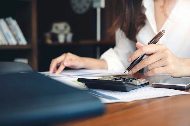 Mujer que usa la calculadora en el escritorio de oficina.