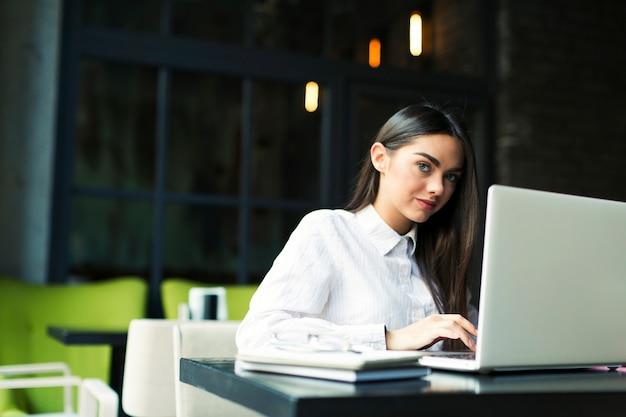 Mujer que usa la computadora portátil en café