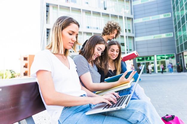 Mujer que usa la computadora portátil para estudios cerca de amigos