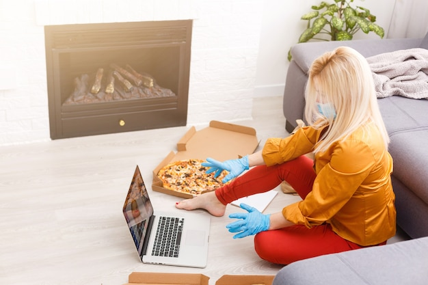 Mujer que usa la computadora portátil para pedidos de alimentos en línea durante la cuarentena, primer plano. servicio de entrega