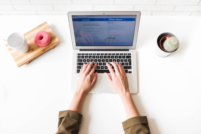 Mujer que usa el sitio social de facebook en la computadora portátil