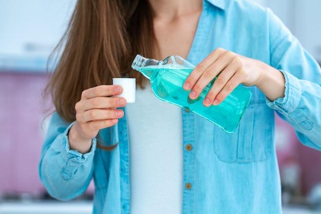Mujer que usa un enjuague bucal para enjuagar la boca y la salud dental. higiene bucal y cuidado dental