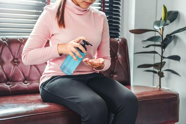 Mujer que usa un gel de alcohol desinfectante para manos para lavarse las manos y prevenir virus y enfermedades en el hogar