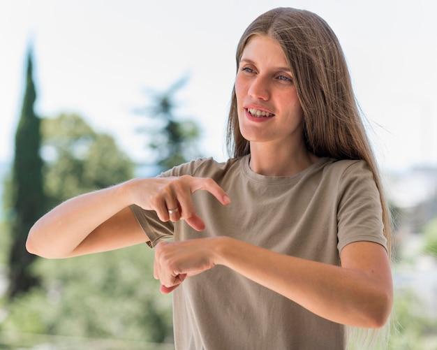 Mujer que usa el lenguaje de señas al aire libre para conversar