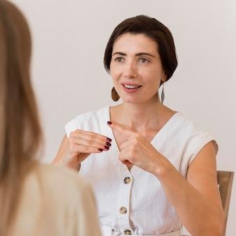 Mujer que usa el lenguaje de señas para comunicarse con su amiga