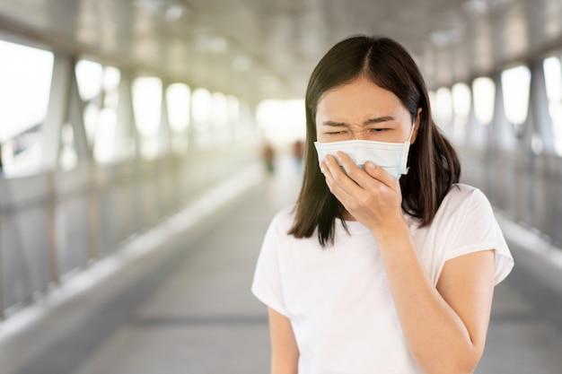 Mujer que usa una máscara protectora de higiene para proteger el virus covid19, covid-19 y pm2.5 mientras viaja en un lugar lleno de gente. la mujer usa una mascarilla para proteger la enfermedad por coronavirus. crisis 2019-ncov.