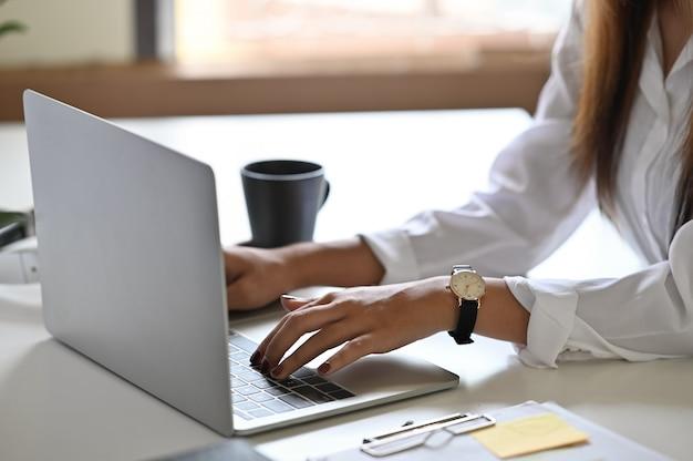 Mujer que usa el ordenador portátil en la tabla con la foto cosechada del tiro.
