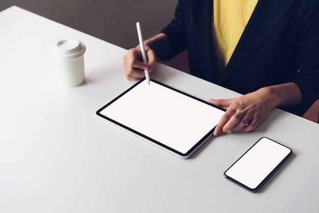 Mujer que usa la pantalla de la tableta y el teléfono inteligente en la mesa simulacro para promocionar sus productos.