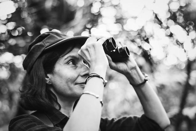 Mujer que usa los prismáticos en el bosque