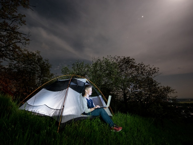 Mujer que usa su computadora portátil con las auriculares en el camping en la noche.