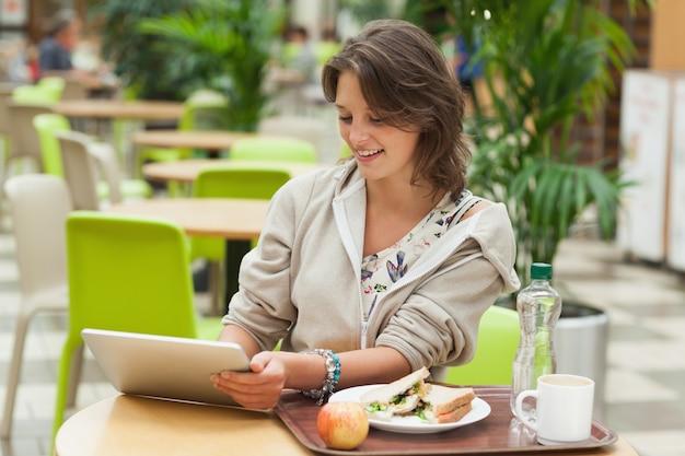Mujer que usa la tableta en la cafetería
