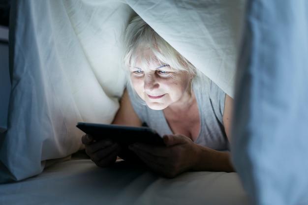 Mujer que usa la tableta debajo de la manta