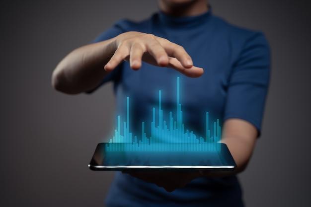 Mujer que usa la tableta de planificación de marketing digital con efecto de holograma gráfico