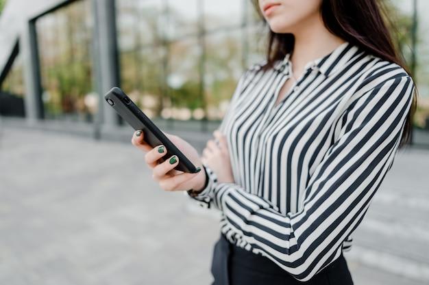 Mujer que usa el teléfono al aire libre