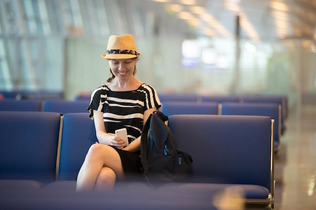 Mujer que usa el teléfono celular en el aeropuerto que espera el salón