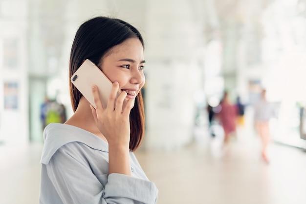 Mujer que usa el teléfono inteligente en la escalera en áreas públicas, durante el tiempo libre.
