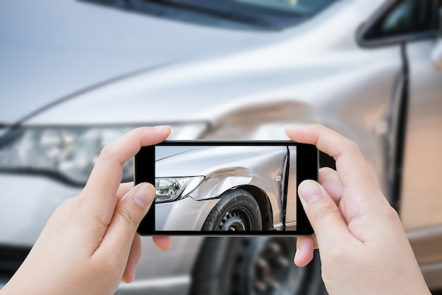 Mujer que usa el teléfono inteligente móvil toma la foto del accidente de coche de los daños al coche para el seguro de accidentes