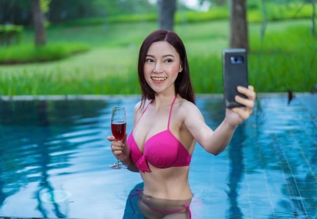 Mujer que usa el teléfono inteligente y que hace la foto del selfie en piscina