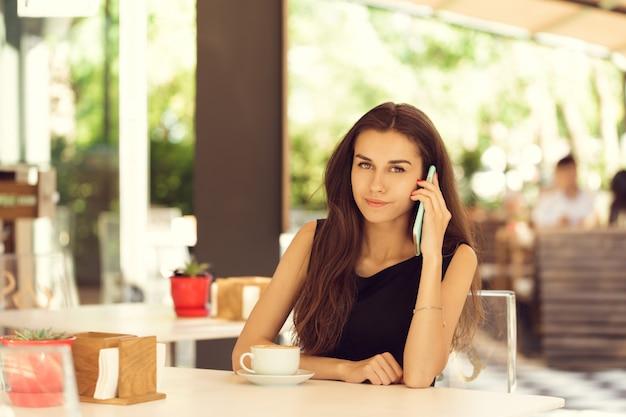 Mujer que usa el teléfono móvil en la cafetería