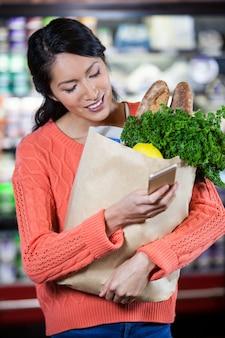 Mujer que usa el teléfono móvil mientras sostiene comestibles