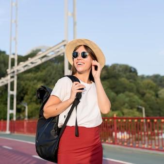 Mujer que viaja sonriente con mochila con sus auriculares
