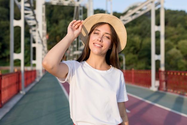 Mujer que viaja sonriente en puente con sombrero